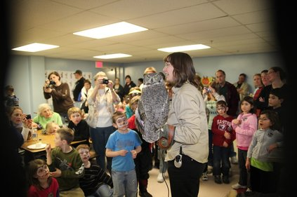 Photo: Karla holds Alice the great horned owl at the first owl festival, as children and adults crowd around.