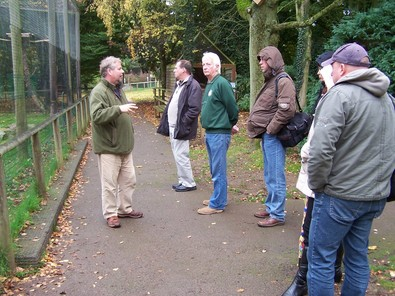 Photo of people standing and listening to a speaker outside an aviary at the hawk conservancy trust.