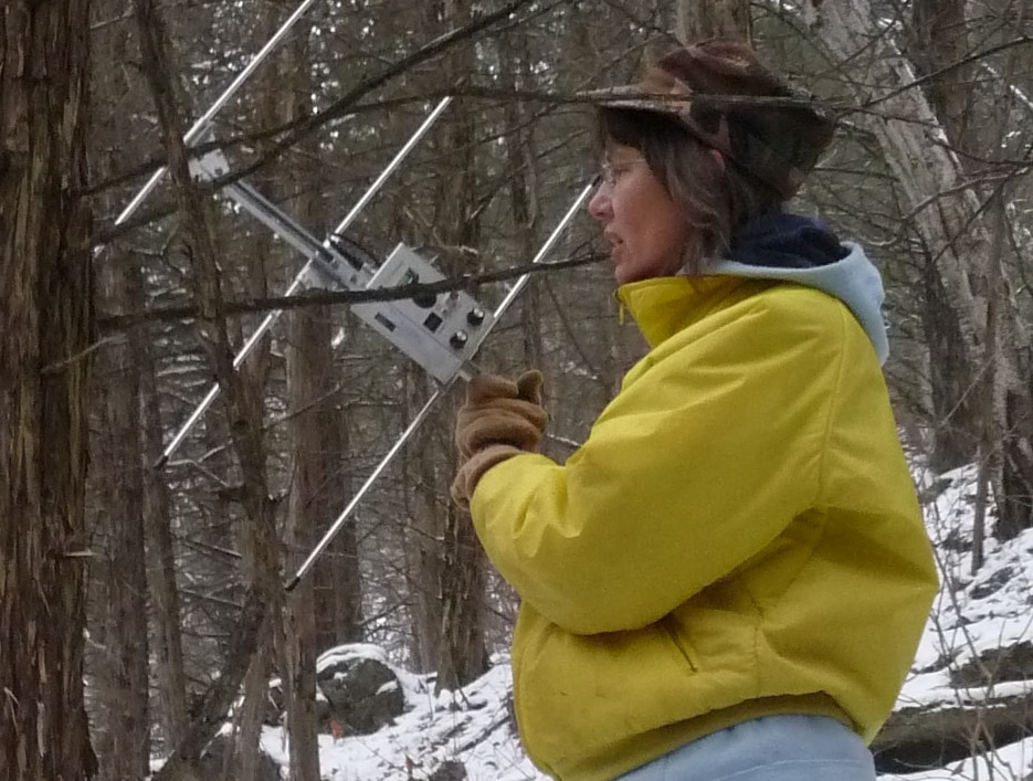 Photo of a woman wearing a yellow jacket and holding a radio telemetry receiver